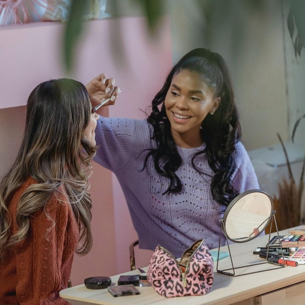 Garota aplica com um pincel sombra nos olhos da amiga em uma mesa cheia de produtos de maquiagem