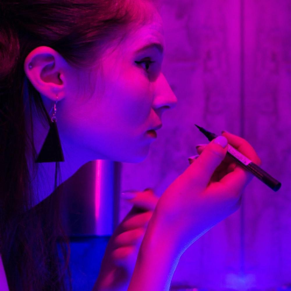 Jovem fazendo uma maquiagem com uma caneta delineadora em ambiente com luz rosa e roxa