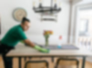 Hispanic male cleaning technician cleaning a kitchen table