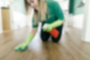 White female cleaning technician cleaning a wood floor