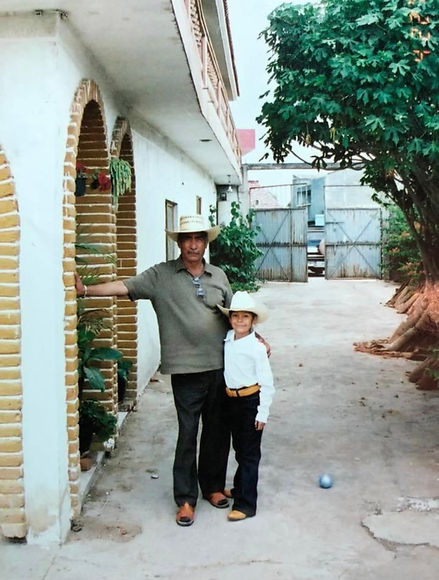Nicole as a child wearing a sombrero and boots is hugging her abuelito, both facing and looking at the camera.