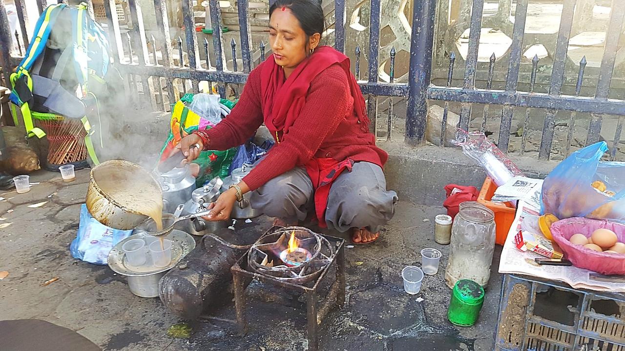 冬の路上でチヤ(ネパールのミルクティー)を売る女性