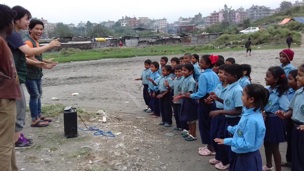 ジャディブティのスクンバシでボランティアとレクリエーションをする子供たち