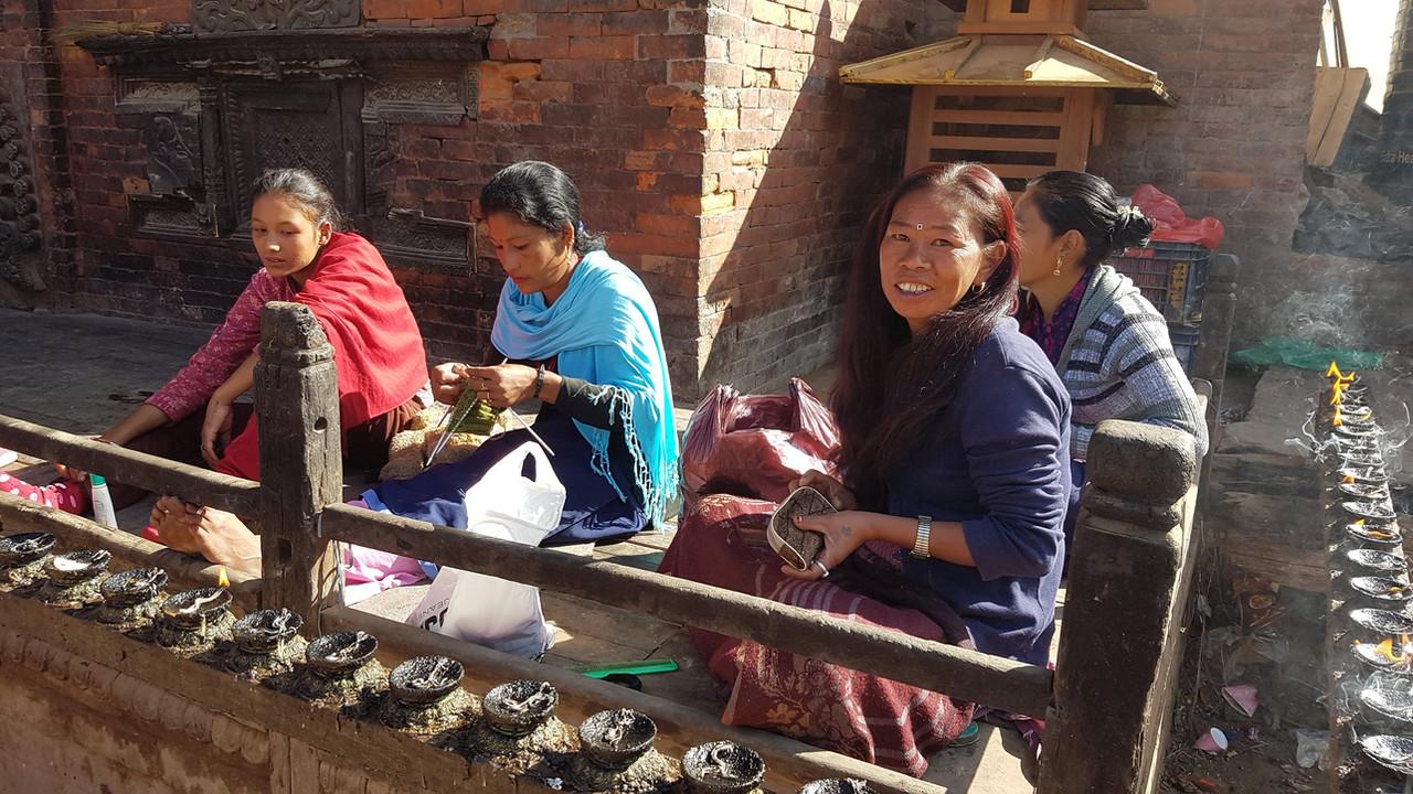 寺院の片隅で、靴下や手袋を編む女性たち