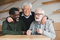 group of multiethnic senior friends embracing in bar.jpg