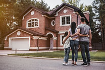 Back view of happy family is standing near their modern house and hugging.jpg