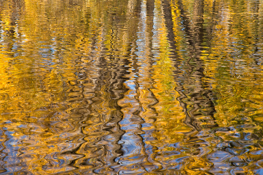 The zig zag reflection is of fall foliage above the water.