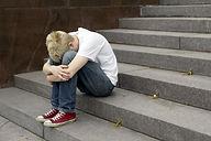 upset young man sitting on stairs put hi