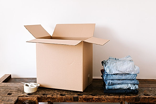 stack-of-jeans-near-carton-box-and-tape-