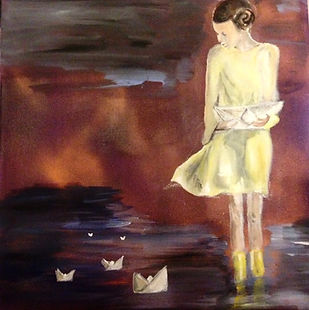 girl in wellies standing in puddle making paper boats