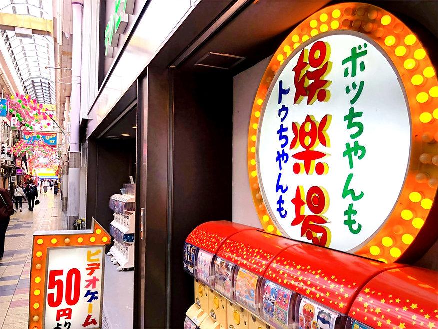 大阪/ゲームセンター『かすが娯楽場』店の入口です。大阪/新世界/ジャンジャン横丁と昭和レトロな「娯楽場」看板が目印。UFOキャッチャーやガチャガチャ/エレメカなどが入口付近にございます。