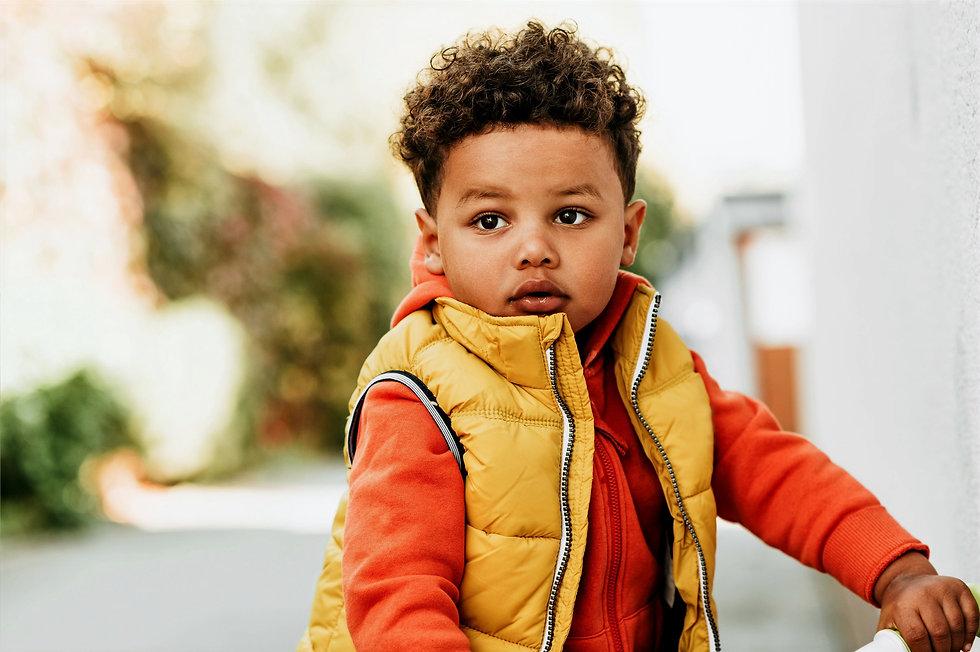 Toddler boy wearing yellow vest and orange hoodie.