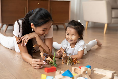 Lying on warm wooden floor asian mom play game with little daughter holds dinosaurs toys h
