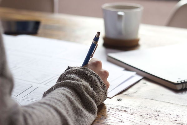 Hand writing on documents, notebook and mug on desk