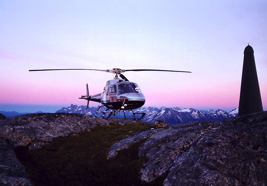 helicopter standing on mountain top with scenery in the background