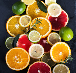 Sliced citrus fruits, vitamins, oranges, grapefruits, limes, juicy fruits background