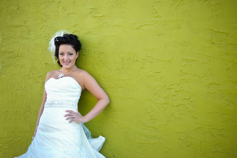 Bride leaning on painted stucco wall
