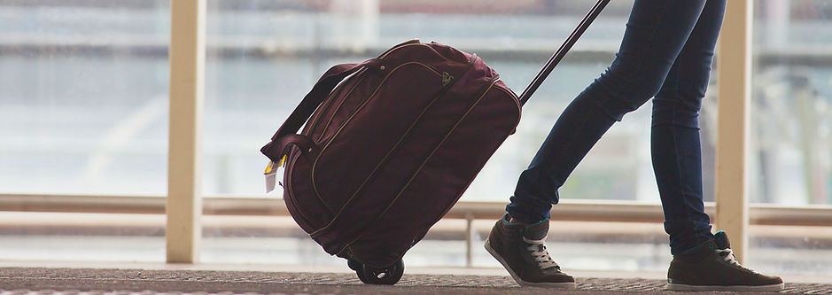 [Image description:] The website's banner depicts a person pulling a maroon coloured duffel bag on wheels. The bag is full, and a yellow tag hangs from its handles. The person pulling the bag is only visible from the upper thighs, down. They're wearing dark wash jeans and brown sneakers with green accents and white laces. There are support beams and floor-to-ceiling windows visible in the background, leading you to believe that this image was captured in a airport.