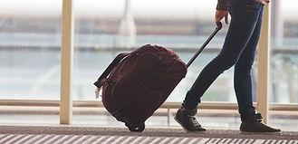 Persona di rotolamento valigia in aeropo