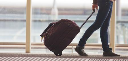 Person Rollkoffer in Flughafen