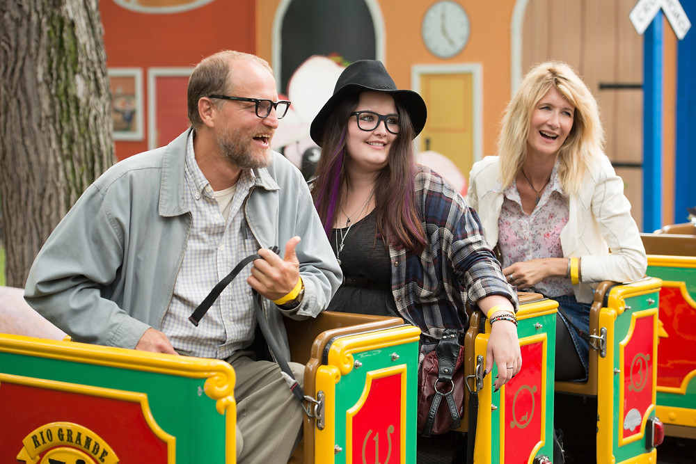 """FILM 101** Wilson – Film Review  Siriol Dafydd  June 2, 2017  Entertainment, Movie Reviews, Movies-What's On Have you ever watched a film and then walked out of the cinema unsure whether you liked it or not? Well, Wilson was a bit like that for me.  Starring Woody Harrelson as the title character, Wilson is a quirky comedy about a socially inept, bitter, middle aged man with a tendency to rub people up the wrong way (and seemingly gets a bizarre, sadistic pleasure out of doing so). A bit like a wannabe hipster who's not quite cool enough to pull it off, Wilson hates most things about modern society along with humans in general but is also driven by an innate sense of loneliness and longing for companionship. This combination does not an easy life make.  Based on a graphic novel of the same name (written by Daniel Clowes), the film follows Wilson's downward spiral of a life over the course of a few years; during which he mourns the death of his father, loses his best friend to suburban St Louis and tracks down his crack-whore ex wife only to find out he has a seventeen year old daughter who she put up for adoption after faking an abortion. (I told you he didn't have an easy life…)  Harrelson does a stellar job overall. He captures the acerbic wit of a cranky bastard (who is probably a little bit on the spectrum) perfectly and delivers some hilarious one-liners and off-beat remarks which had me laughing out loud (with the occasional snort) throughout. He's joined by a very strong cast including Laura Dern (Jurassic Park, Wild & Big Little Lies), Cheryl Hines (best known as Larry David's wife in Curb Your Enthusiasm) and Judy Greer (bug-eyed quasi-ginger who pops up in most romantic comedies as the sassy best friend). Along with cameos by Margo Martindale, Mary Lynn Rajskub and Brett Gelman, a noteworthy performance is also delivered by star on the rise, Isabella Amara as Wilson's 'chip off the old block' social outcast of a daughter.   Woody Harrelson as """"Wilson"""", Lau"""