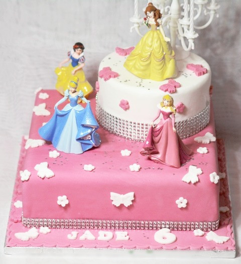 A Stunning Two Tier Birthday Cake With 4 Beautiful Keepsake Princesses And Candelabra It Will Be Centre Attraction At Any Celebration