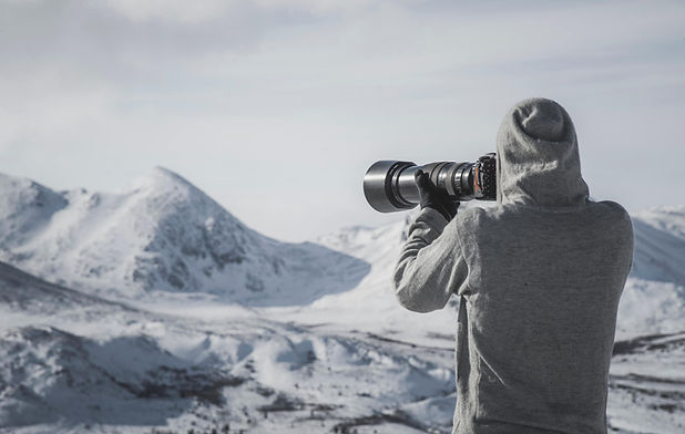 Photographer with a big Telephoto lens takes pictures of snowcovered mountains