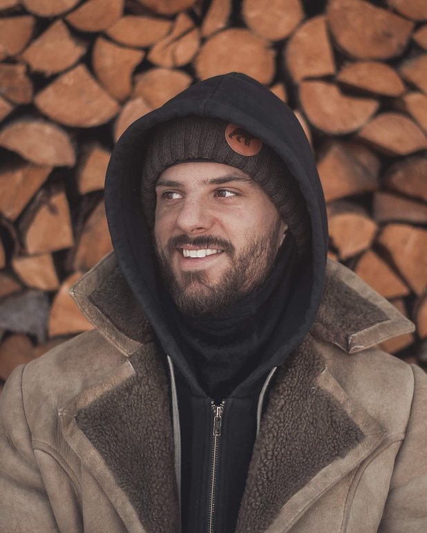 Guy sitting in a sheepskin coat in front of a pile of firewood and smiles