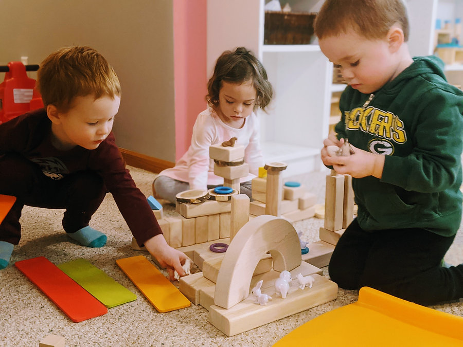 Children building with blocks and small animal toys. Copyright Olson Family Child Care