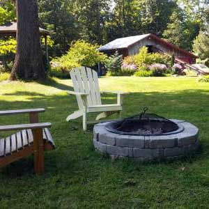 Outdoor fire pit wit adirondack chairs on the lawn