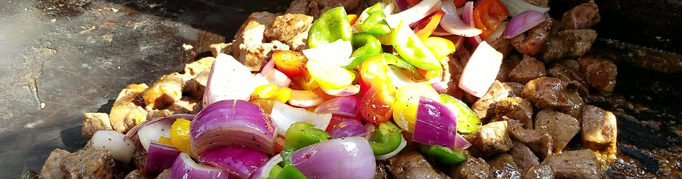 Steak Tips and vegetables sizzling on the grill.