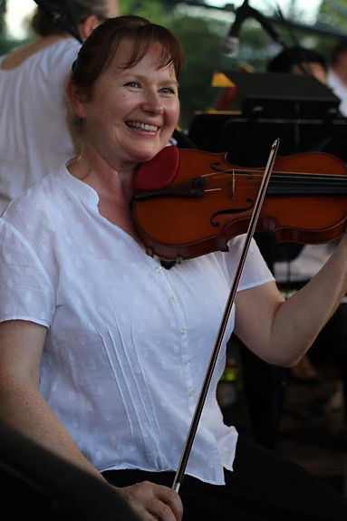 Violinist Tatiana Karpova, a musician of the Charlotte Symphony, flashes a smile while warming up