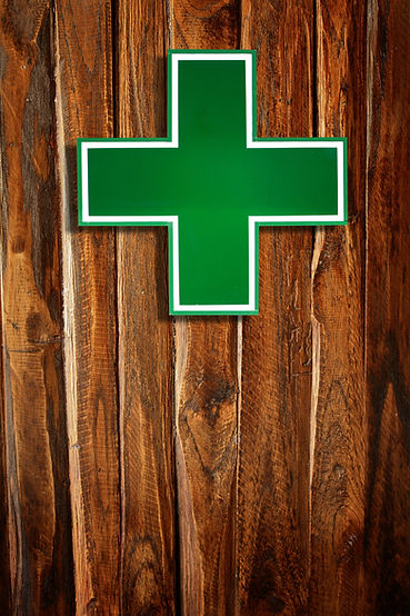 Green medical cross sign on wooden background