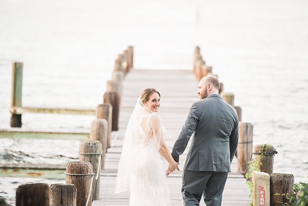 bride and groom walking on pier