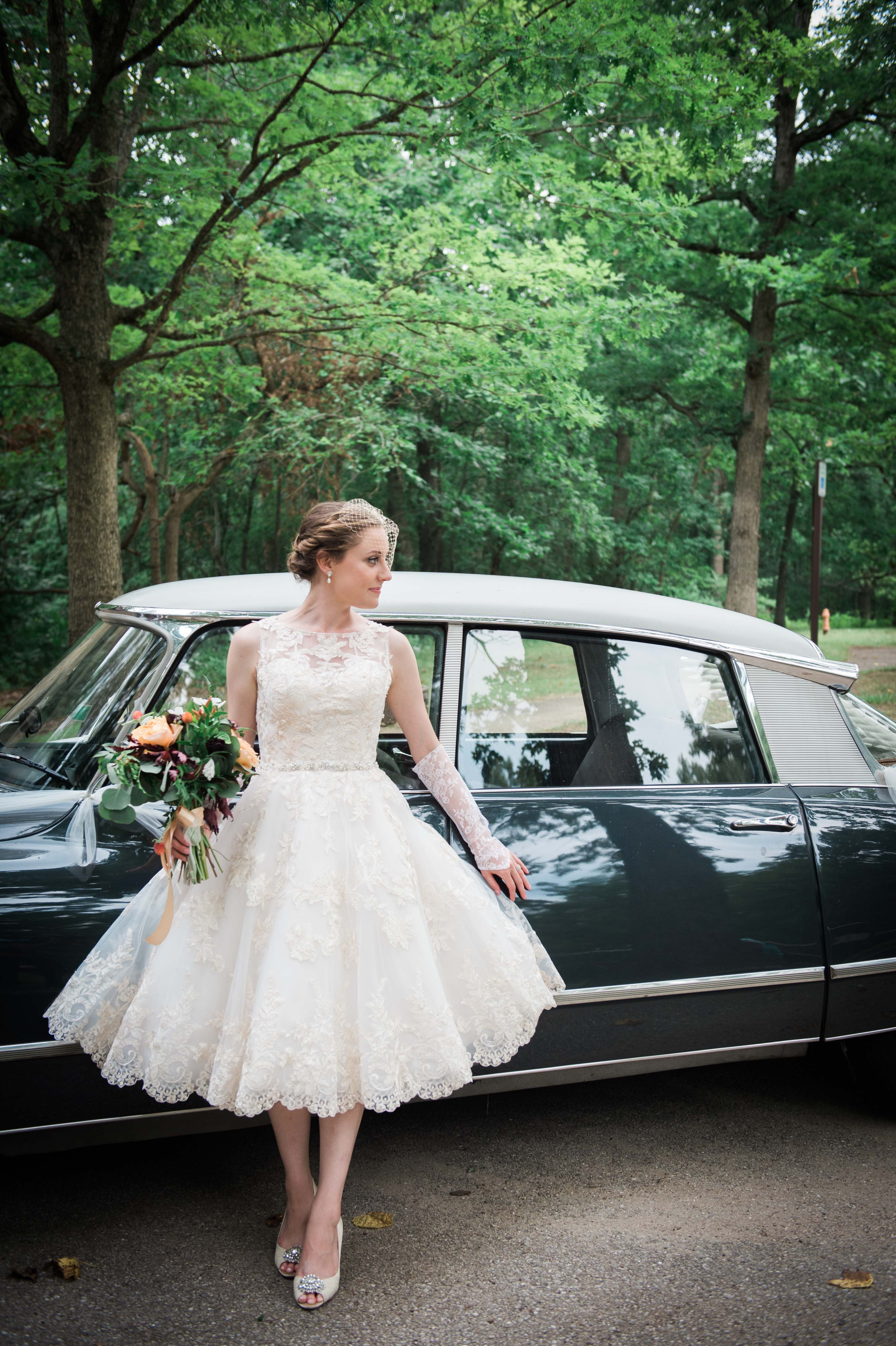 Bride leaning on vintage car