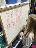 Girl writing on white board