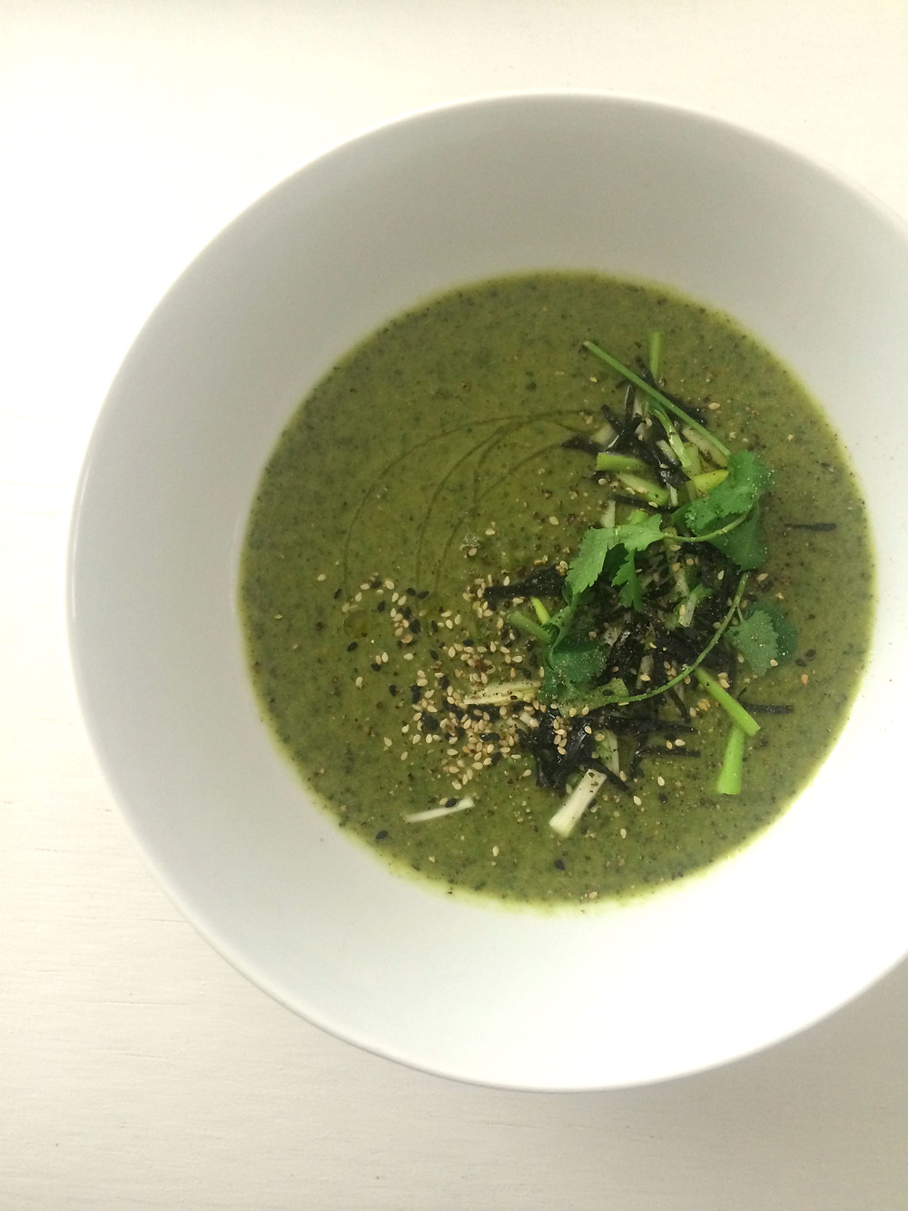 Broccoli soup topped with sesame seeds, nori and coriander