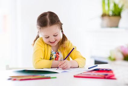 Cute little girl doing homework, reading