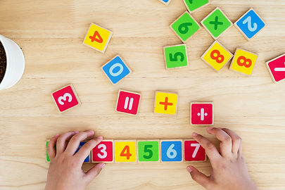 Child Hand With Wooden Toy Plate Numbers