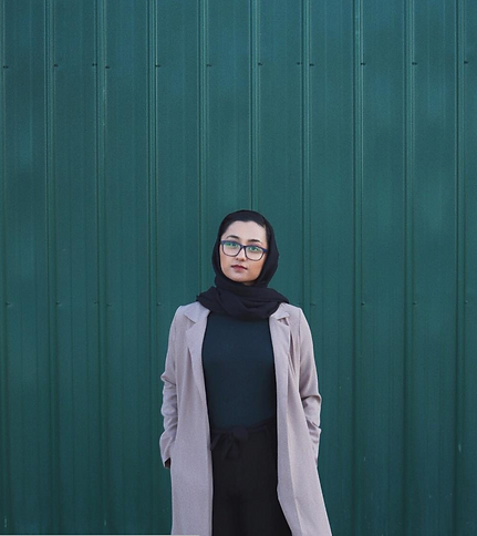 A picture of a girl wearing a hijab, a green shirt, black pants, and a beige coat