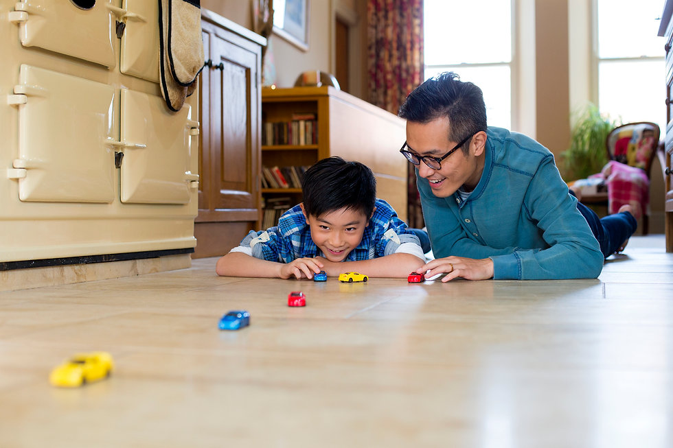 man on floor playing cars with son
