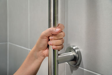 hand holding a grab bar in shower