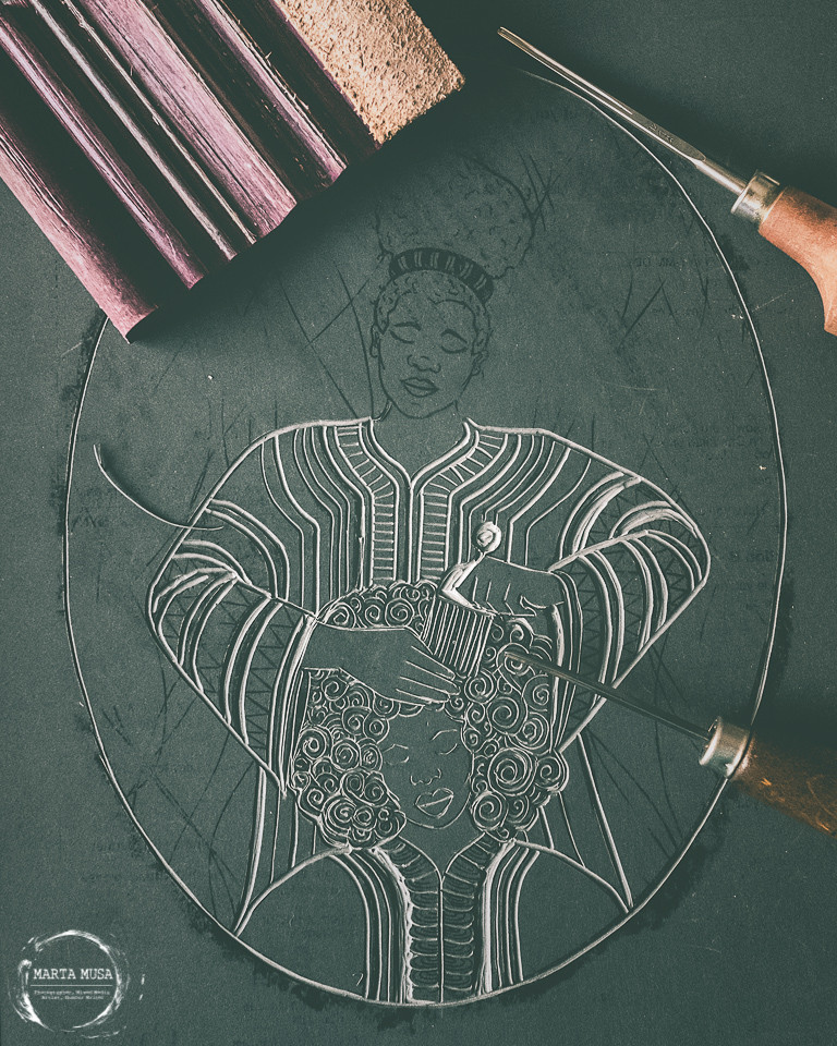 A photograph of a linoprint block in half carved out.  The block print appreas to be the beginning of a plate of a seated african woman having her hair combed by another African woman who is stood behind her.  There are carving tools and a sharpening block towards the edges of the frame.