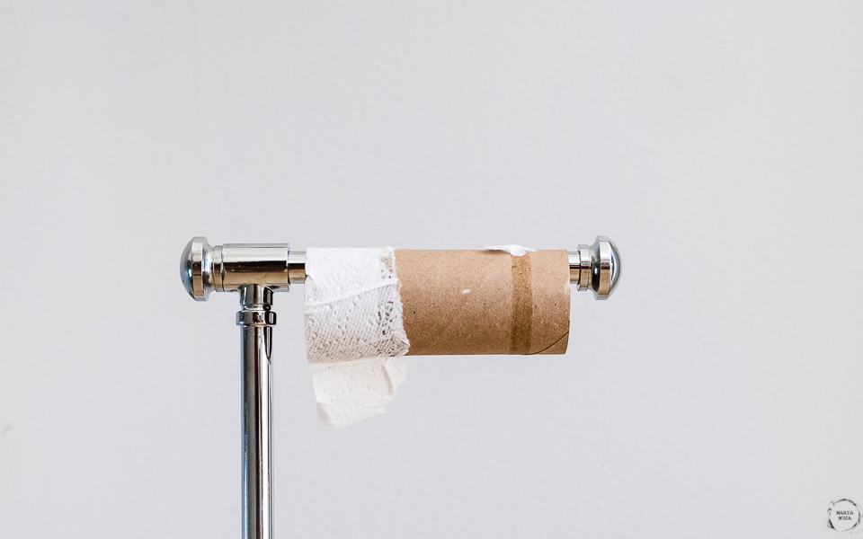 Toilet paper roll with a third of a sheet of Toilet paper on it, sitting on a toilet paper stand