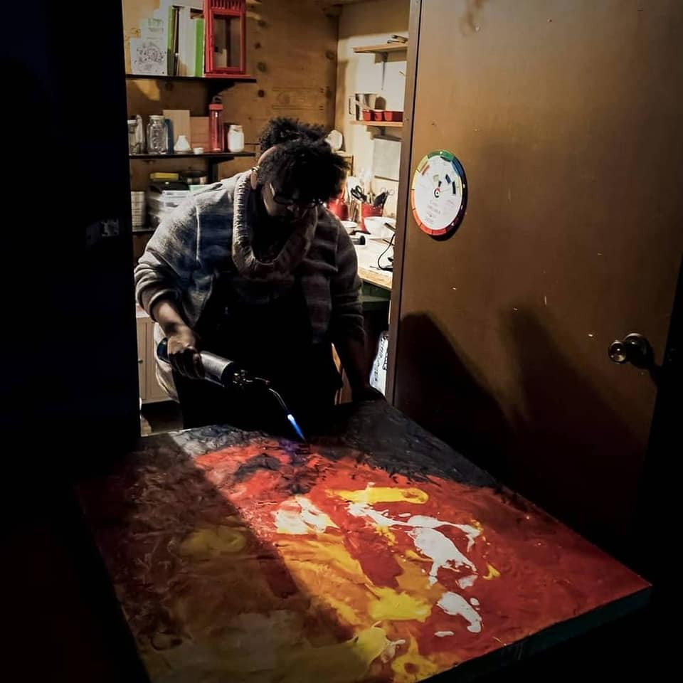 A night time image of Marta working on a large painting in an uninsulated shed.   There light from only one light bulb.  And Marta is wearing multiple layers of clothing to keep warm on this cold night.