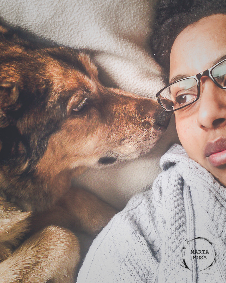 An image of a 15 year old dog, Kootney, a husky shepherd cross, and the author Marta Musa laying together