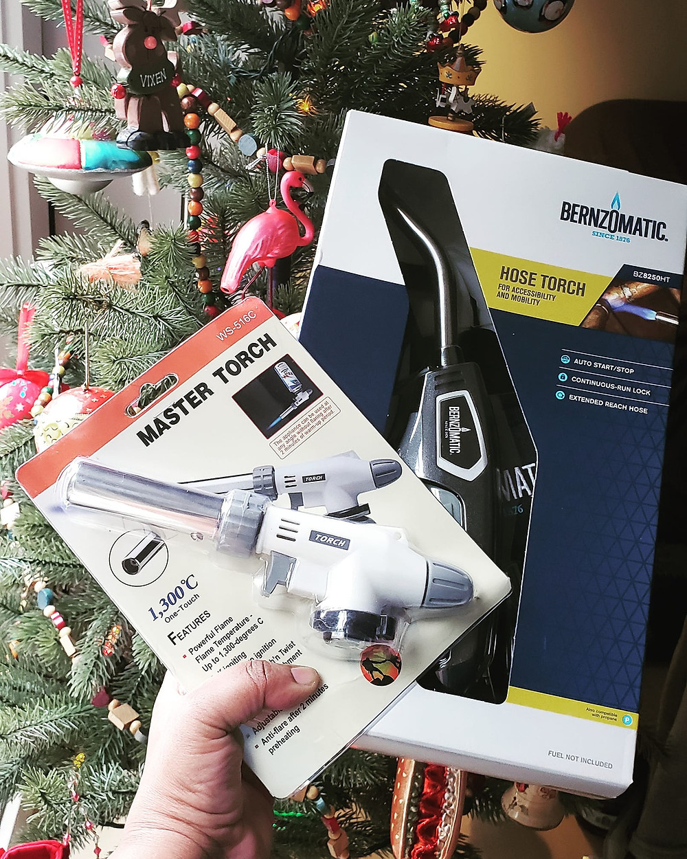 A photograph of a Butane torch head and a Propane torch head in front oa  christmas tree.