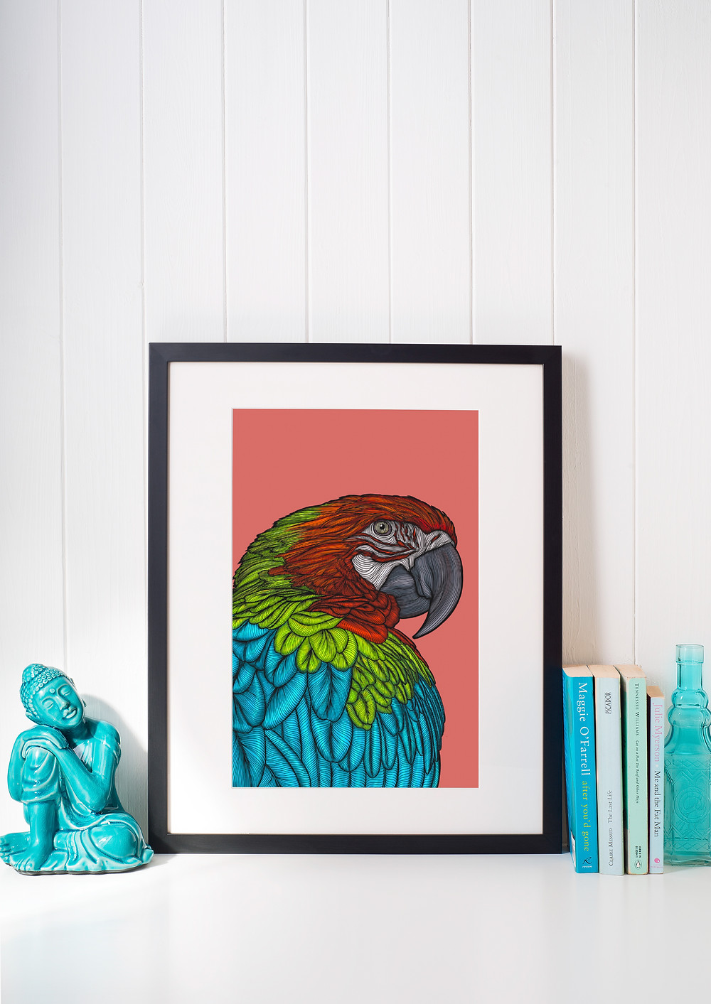Contour drawing of a Macaw in a large Black Frame on a shelf with books and a small sculpture