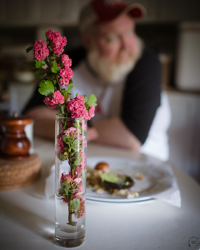 Vase with Blossoms in the foreground and an out of focus outline of a bearded white man in the background