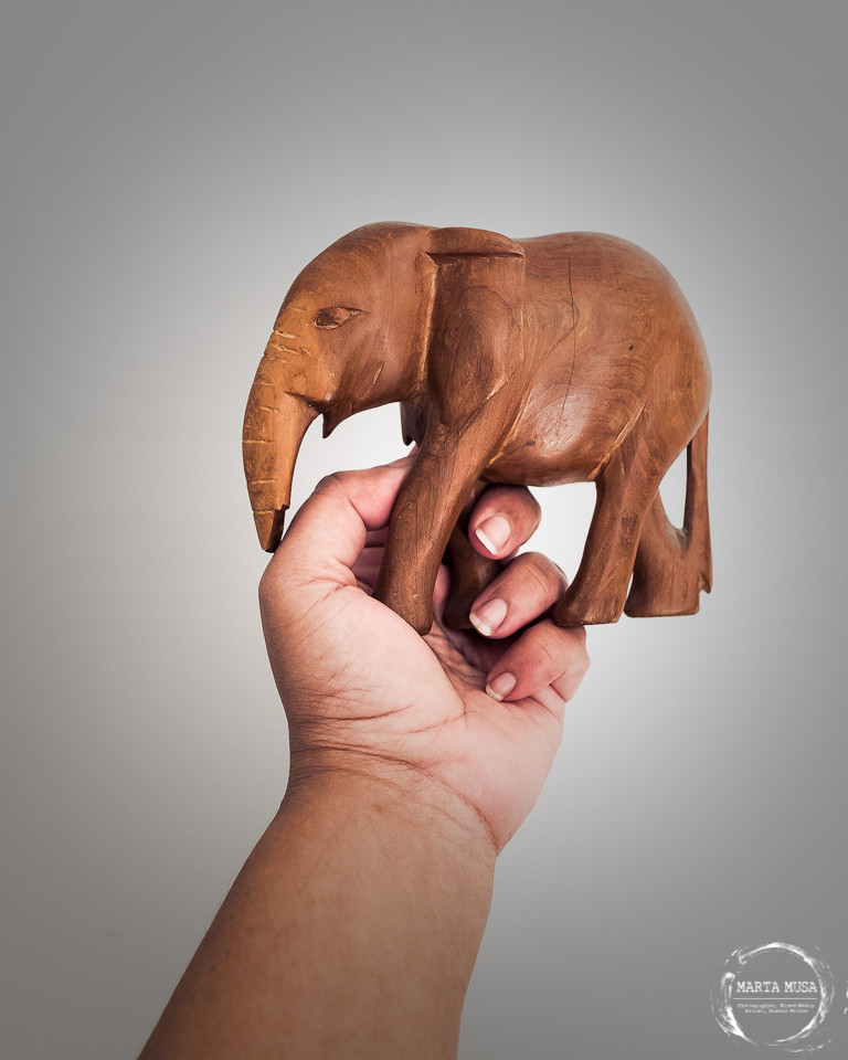 A photograph of a black woman's left hand holding up a wooden carving of an African Elephant.  Shot against a grey background